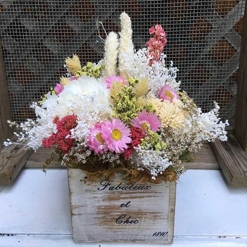 Caja de madera vintage con flores secas y preservadas