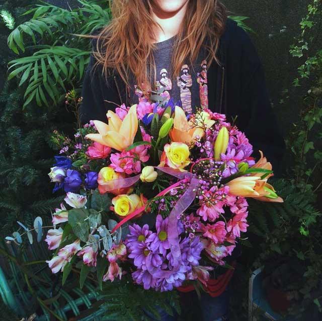 IXIA-- Bouquet en tonos naranjas, rosas y lilas compuesto con lilium naranja, rosas naranjas, iris lila, alstromerlia rosa y crisantemo variado