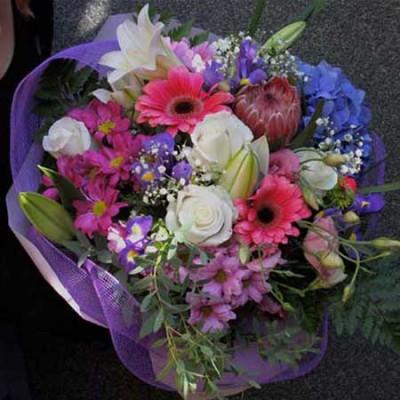 Bouquet en tonos rosas, blancos y lilas con rosas blancas, lililum blanco, gerberas rosas, iris, protea, hortensia azul, lisianthus rosa y cristantemo.