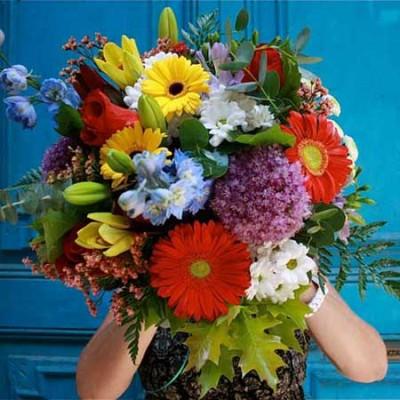 Bouquet en tonos rojos, amarillos y naranjas compuesto por anthuriums rojos, gerberas amararillas, rosas rojas, celosias, cristantemo y lilium blanco.