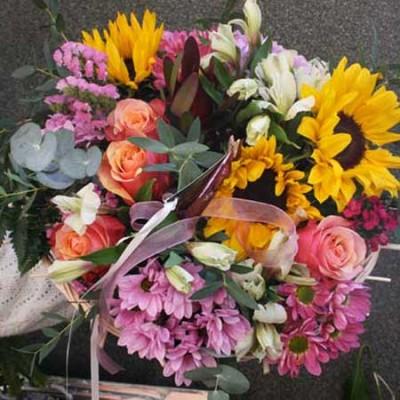Bouquet realizado en una estructura compuesto con girasoles, rosas naranjas, crisantemo, statice y clavel poet.