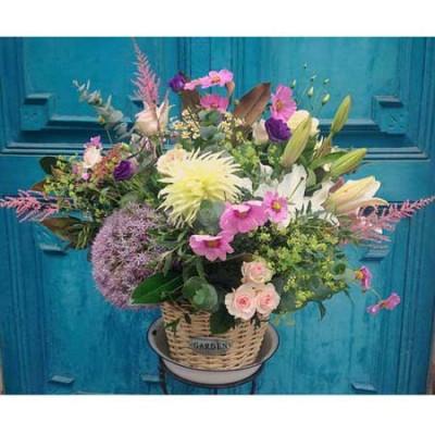 Centro de flores en una cesta de mimbre compuesto por alstileb, allium, dhalias, lilium, lisianthus y rosas de jardín.