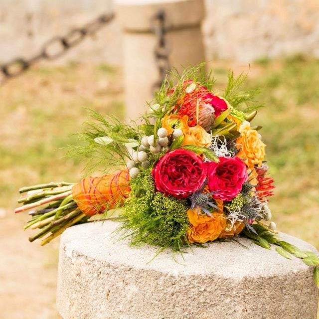 Ramo de novia atrevido y fuerte en tonos naranjas, fucsias y verdes compuesto con rosas david austin, proteas, rosas y crasperia