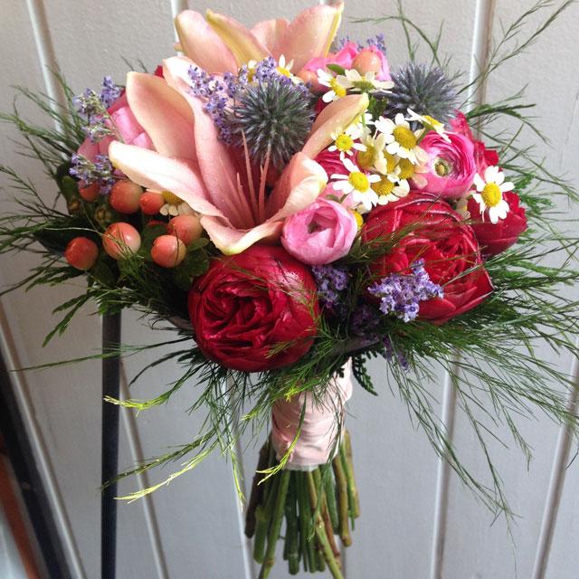 Ramo de novia en tonos azules, fucsias y rosas realizado con lilium, hypericum, peonias y ranunculos