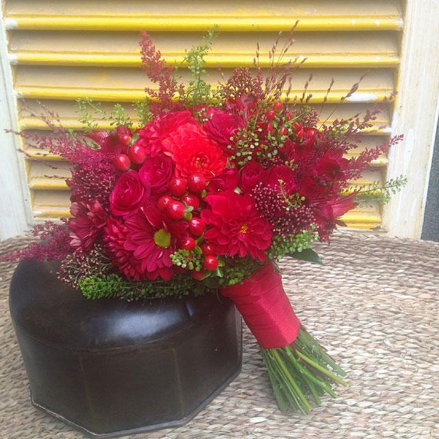 Ramo de novia en tonos rojos realizado con dhalias, rosas, crisantemo y astilbe