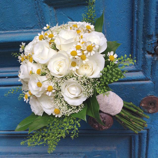 Ramo de novia fresco y elegante en tonos blancos, compuesto por rosas blancas y tanacetum