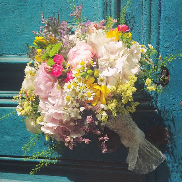 Ramo de novia silvestre y vaporoso en tonos rosas, blancos y amarillos, realizado con peonias, hortensia rosa, freesia y limonium
