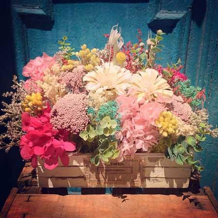 Caja de madera blanca decorada con flor preservada y seca en tonos blancos, fucsias, rosas y amarillos. Es un centro de tamaño grande, ideal para colocar en una mesa. Los materiales utilizado están tratados