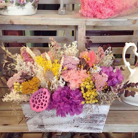 Caja de madera con flor seca y preservada en tonos lilas, amarillos y rosas