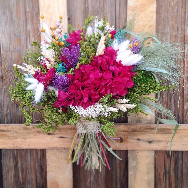 Ramo de estilo campestre, realizado con flores secas y preservadas en tonos fucsias, lilas, verdes y blancos. Es de tamaño grande. No necesita mantenimiento ni agua.