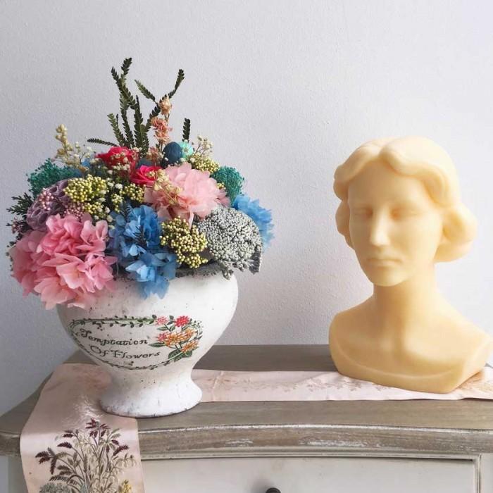 Centro en tonos azules y rosas, con flores secas y preservadas en recipiente de cerámica vintage.