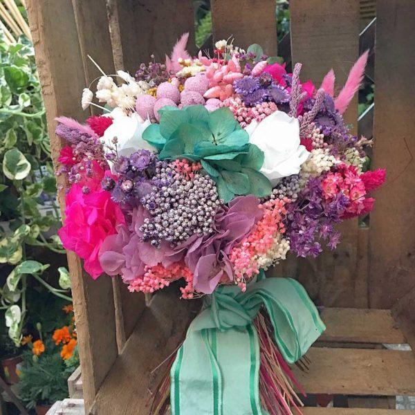 Ramo de novia diferente y atrevido realizado en tonos turquesas, fucsias, blancos y rosas. Está realizado con flores preservadas y secas.