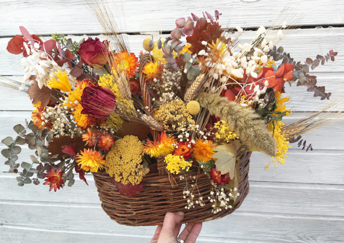 Cesta de mimbre decorada con flores secas en tonos naranjas y amarillos, rosas secas y eucalipto preservado. Composición rústica y de larga durabilidad. Mantener en un lugar alejado de la luz directa. No limpiar con agua, utilizar un secador para quitar el polvo y la suciedad.
