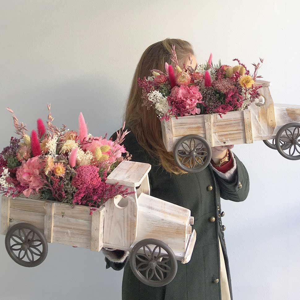Centros florales con flor seca y preservada, camiones de madera decorativos