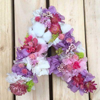 LILAC, letra decorada con flores secas en tonos lilas, blancos y rosas