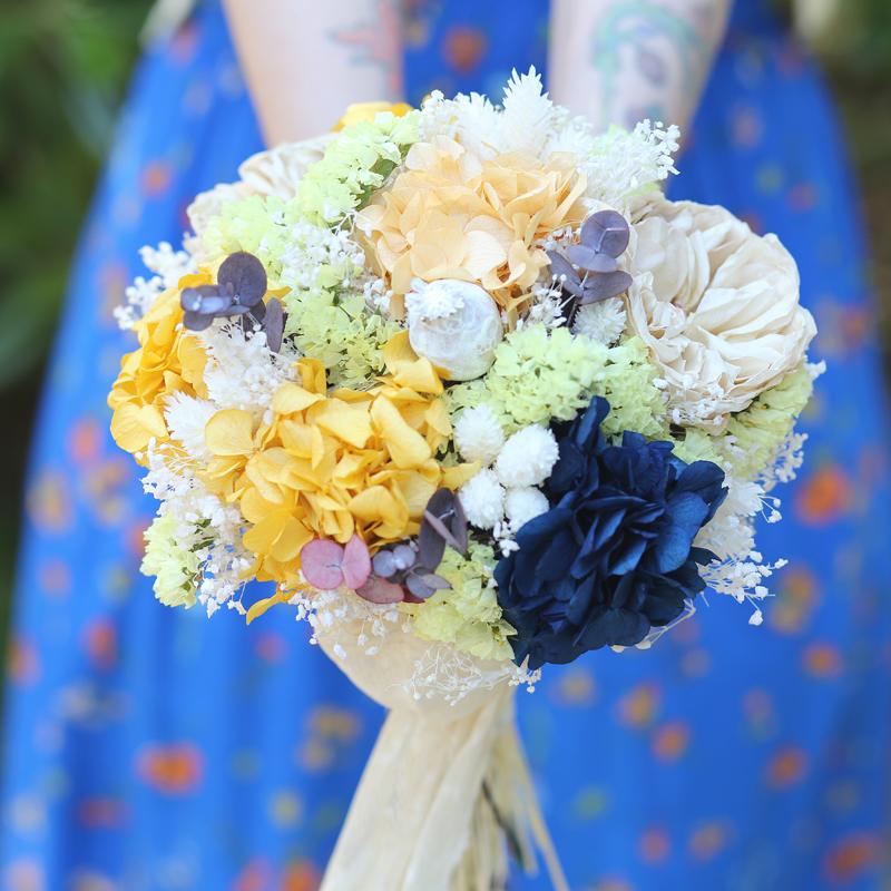 Diferente y original ramo de novia preservado y seco en tonalidades ocres, naranjas, blancas, amarillas y con una nota azul.