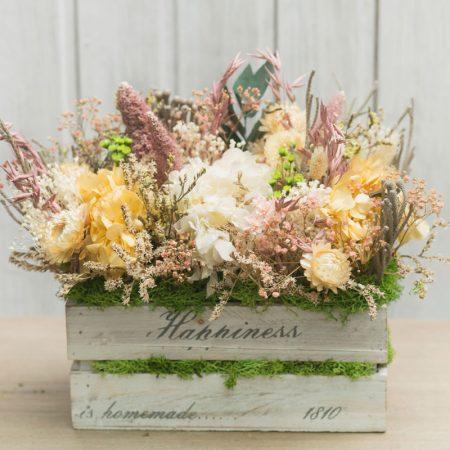 Caja de madera con flor seca en tonos ocres y anaranjados