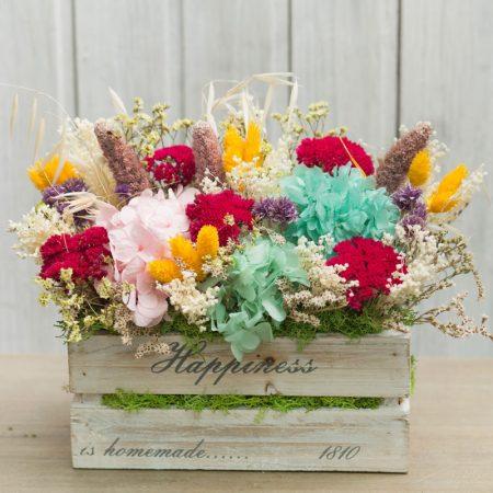 Caja de madera decorada con flor seca y preservada en tonos rojos y turquesa