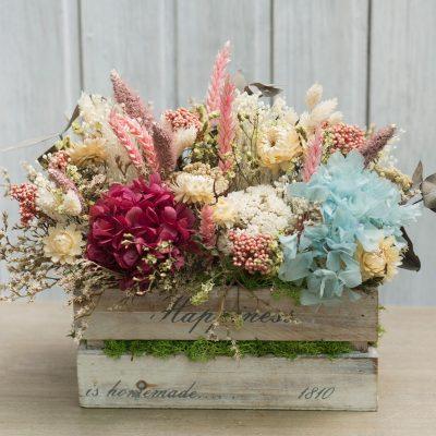 Caja de madera decorada con flor seca y preservada en tonos beig y ocres con toques de rojo y turquesa
