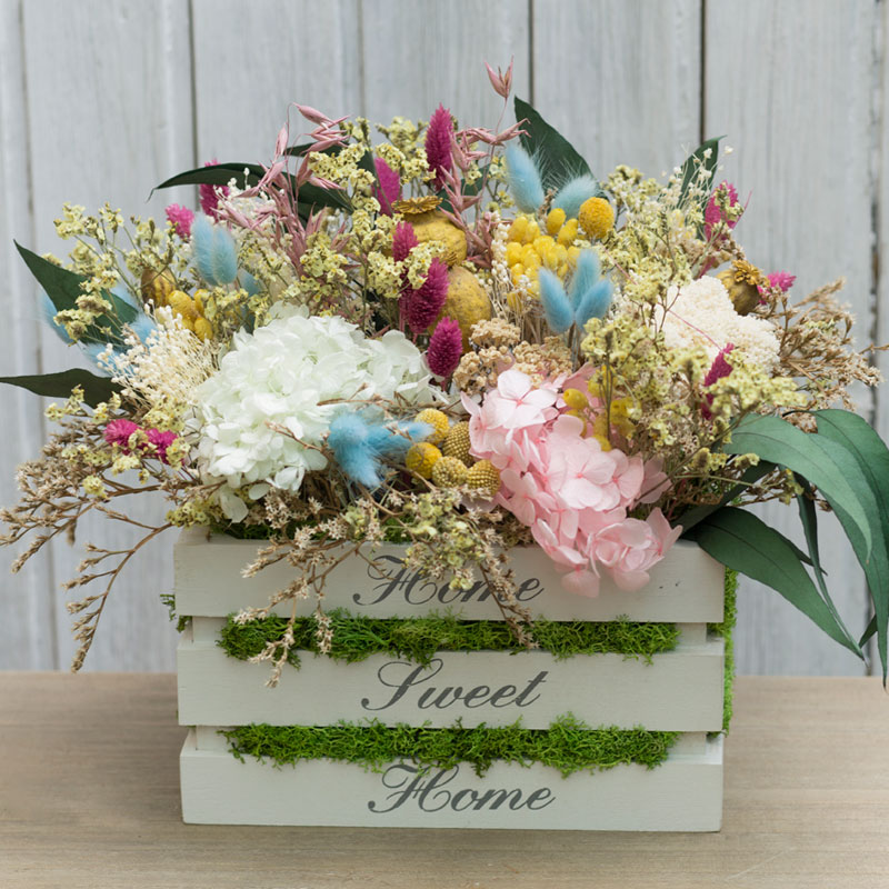 Caja de madera decorada con flor seca y preservada en tonos variados, con verde