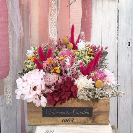 Caja de madera rústica con flor seca y preservada en tonos rosas, rojos, amarillos y verdes