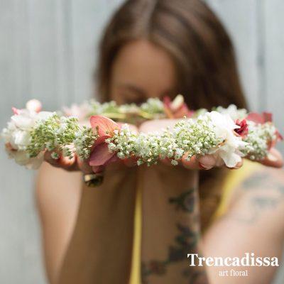 Corona de flores realizada en tonos blancos, rosa sweet y burdeos