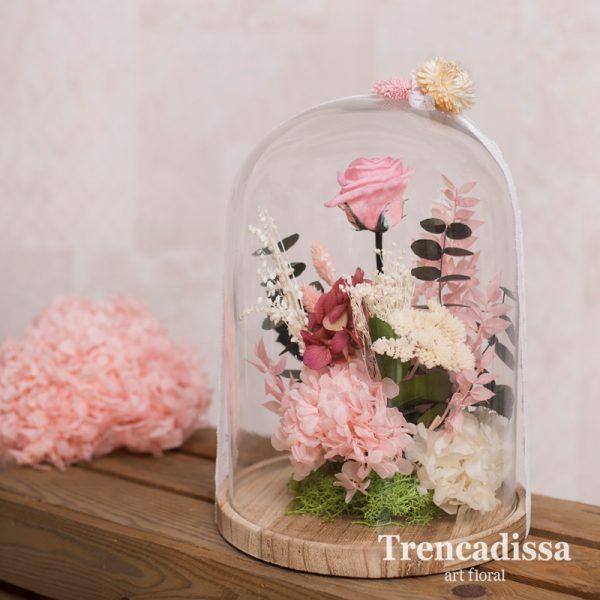 Cúpula o campana de vidrio con flor seca y preservada en tonos rosados