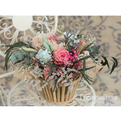 Caja de madera de forma circular con flor preservada en rosas y azules