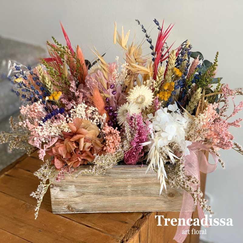 Caja de madera con flor preservada en tonos variados