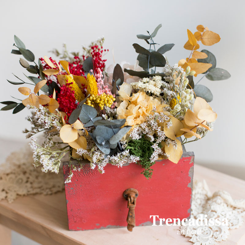 Caja de madera roja con flor seca y preservada