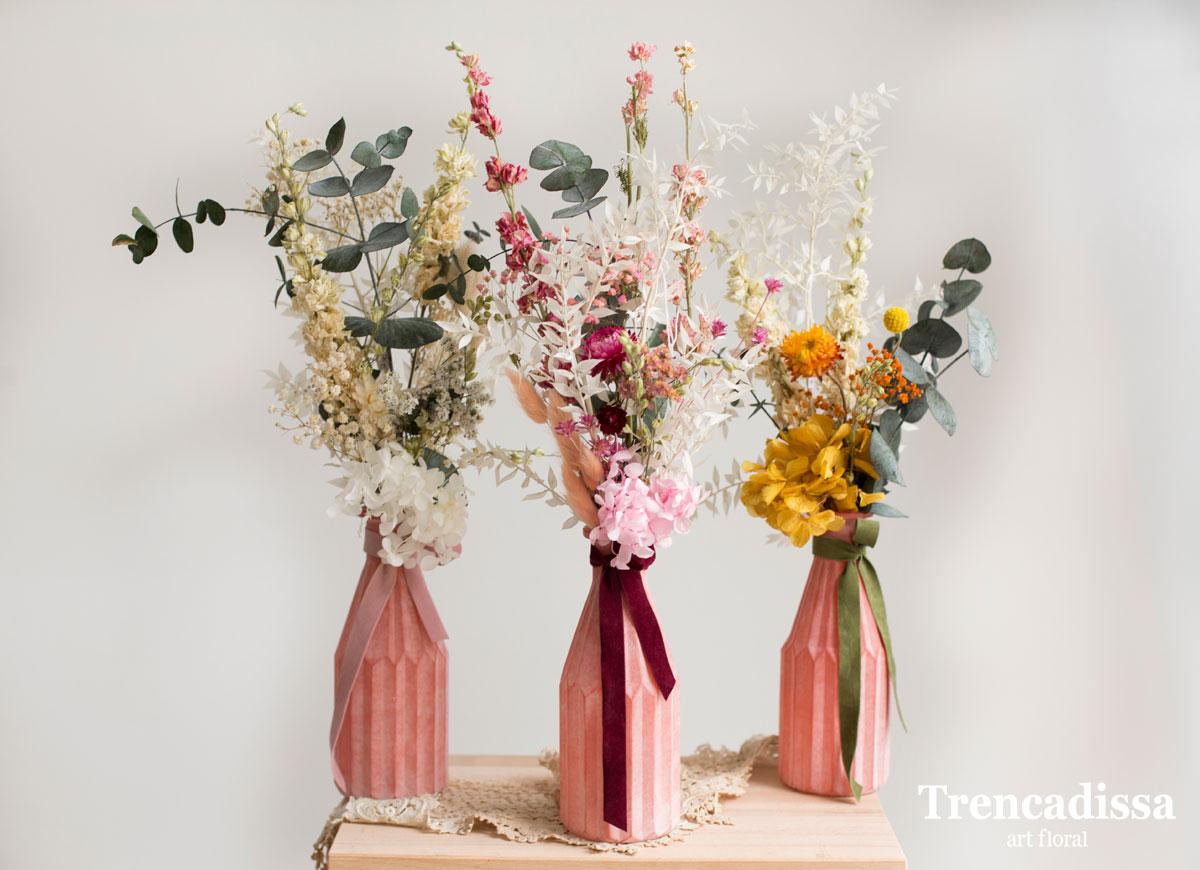 Jarrones de vidrio rosa con flores preservadas