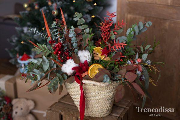 Composición natural realizada en un cesto de fibra natural decorado con motivos navideños.