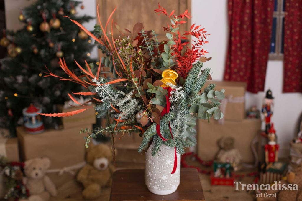 Ramo de navidad natural en un jarrón de cemento con notas navideñas, ideal para decorar y perfumar cualquier espacio.