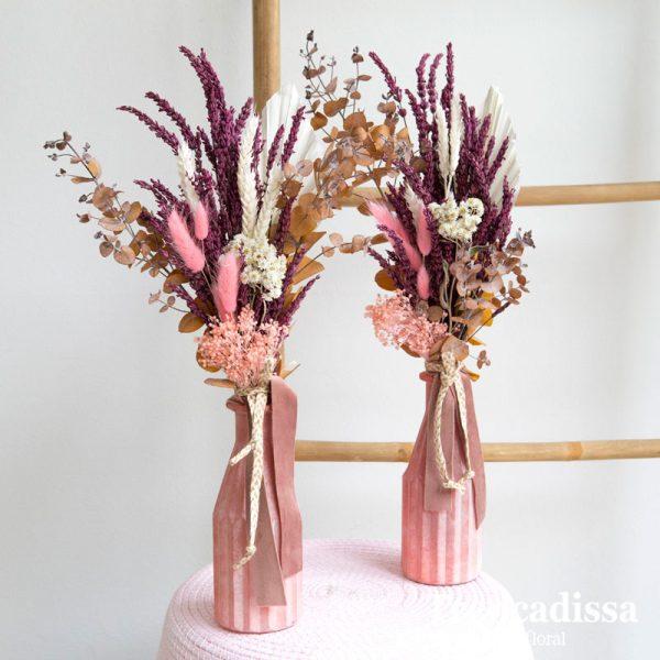 Botella de cristal de color rosa decorada con lavanda preservada rosa, eucalipto ocre preservado, flor seca y palmito blanco