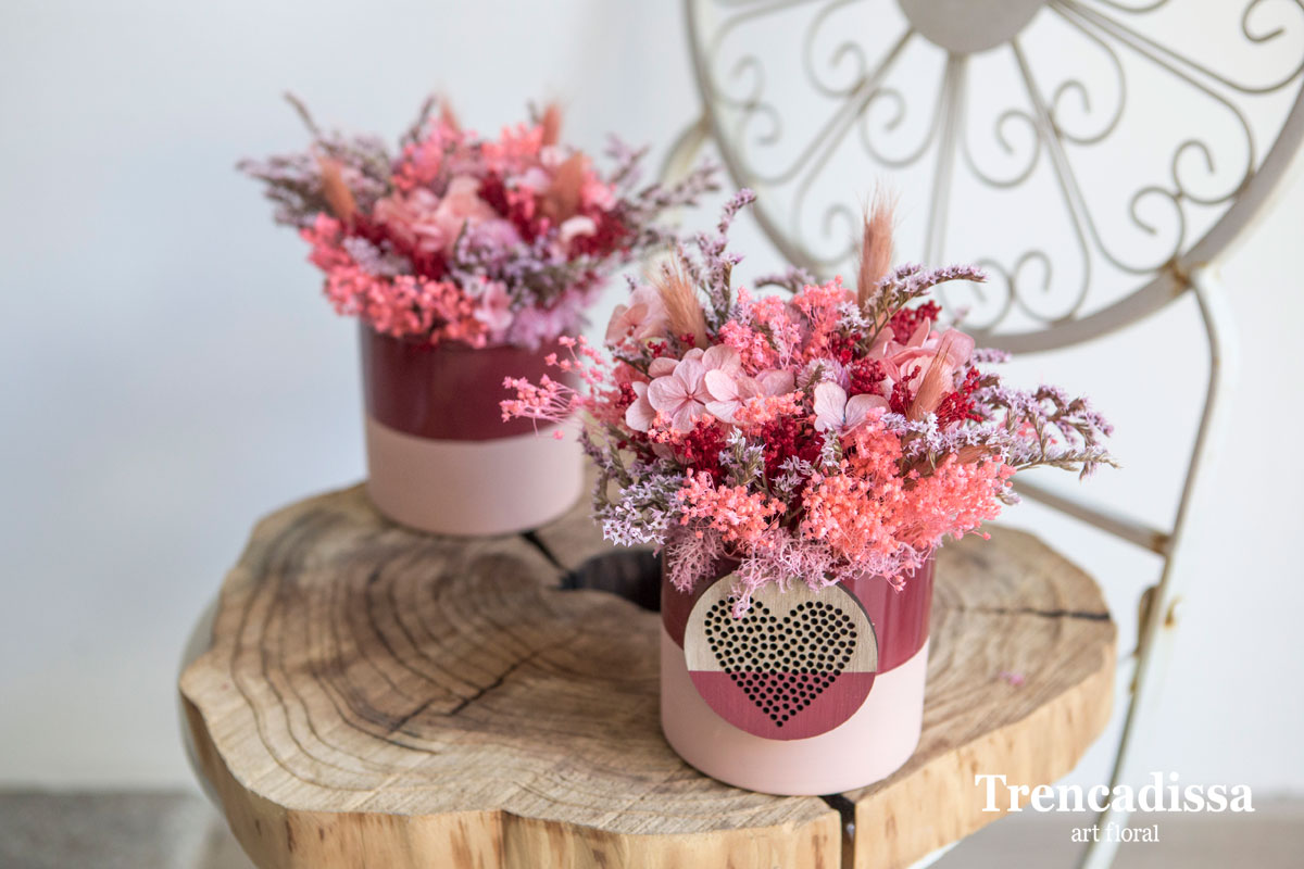 Recipiente de cerámica en tonos rosa y rojo decorado con hortensia preservada y flor seca con corazón decorativo.
