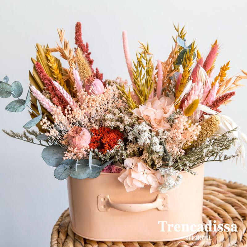 Recipiente metálico color salmón con flor seca y preservada