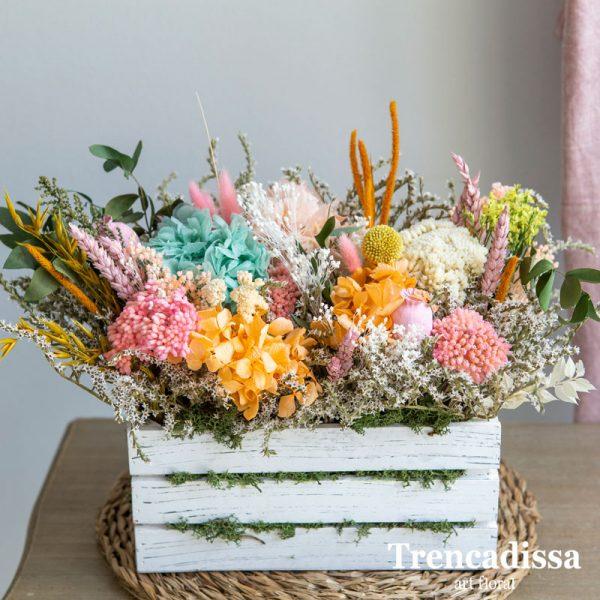 Caja de madera blanca con flor seca y preservada