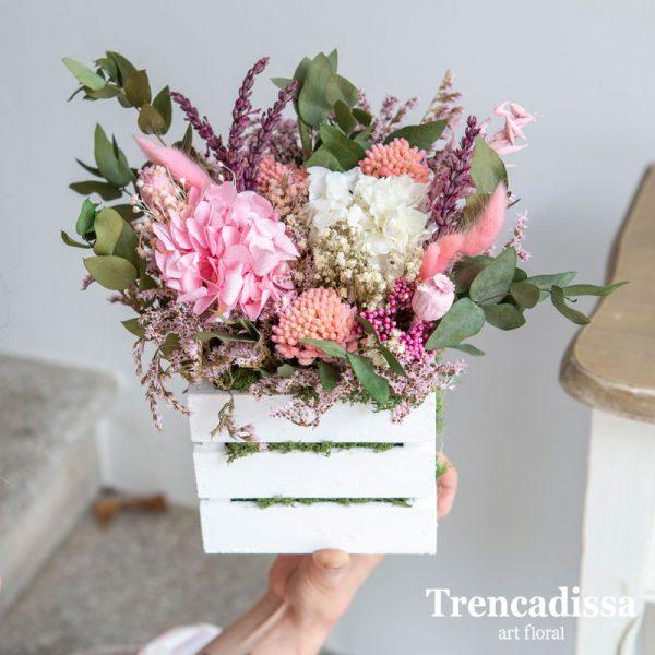 Caja de madera con flor preservada en tonos rosa, verde y amarillo