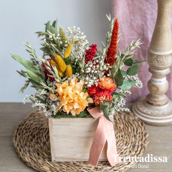 Caja de madera con flor seca y preservada en tonos naranja y granates